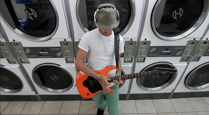 Un chitarrista suona una Carparelli con pre amp e multieffetto incorporati in una laundry